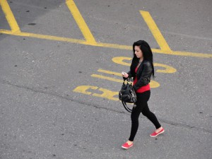Nichtsahnend sucht die Dame etwas in ihrer Handtasche
